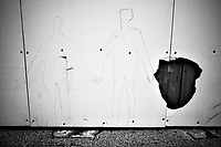 """Switzerland. Canton Ticino. Lugano. A graffiti of a couple holding hands on a construction wall. Nobody in the streets. Due to the spread of the coronavirus (also called Covid-19), the Federal Council has categorised the situation in the country as """"extraordinary"""". It has issued a recommendation to all citizens to stay at home, especially the sick and the elderly. 14.03.2020 © 2020 Didier Ruef"""