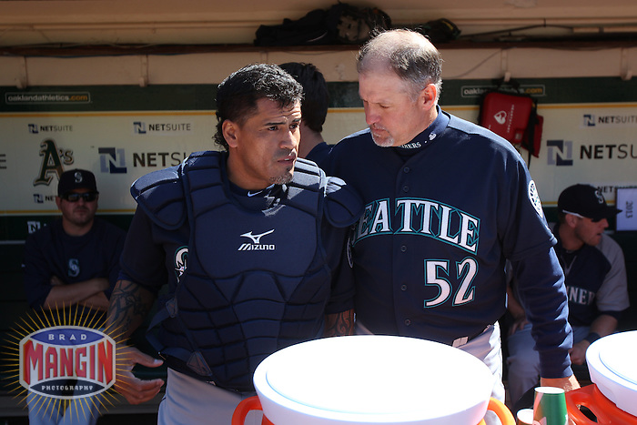 OAKLAND, CA - JUNE 15:  Henry Blanco #33 and coach Daren Brown #52 of the Seattle Mariners talk in the dugout before the game against the Oakland Athletics at O.co Coliseum on Saturday June 15, 2013 in Oakland, California. Photo by Brad Mangin