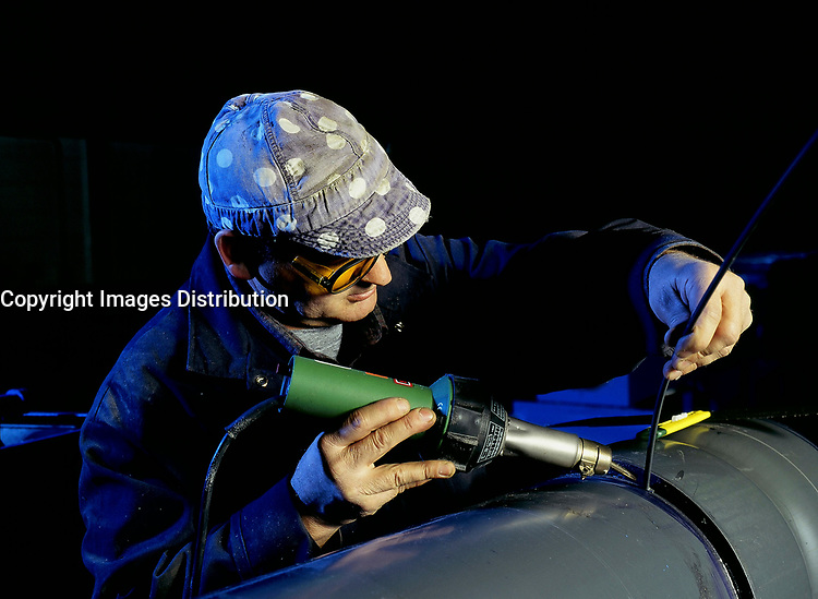 Model released  File Photo<br /> <br /> A welder use heat to solder plastic pipes<br /> <br /> Mandatory Credit: Photo by Pierre Roussel- Images Distribution. (©) Copyright 2004 by Pierre Roussel <br /> <br /> NOTE : scan from 2 1/4 slide