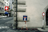 Switzerland. Zoug. The first of august is the swiss national day. Swiss flag and zoug flag (blue and white) float in the old town. Two road signs (a dead end and a no access) are in the street.  © 1989 Didier Ruef