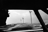 France. Drôme Department. Montélimar. The photographer Olivier Vogelsang is driving a car on the highway A7 (Autoroute du Soleil) ans passes by a group of three aeolian windmills. 06.09.99 © 1999 Didier Ruef