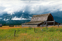 Scenic landscape of an old wooden barn set on a grassy pasture overlooking the Grand Teton mountain range engulfed by white clouds. Jackson Hole, Wyoming.