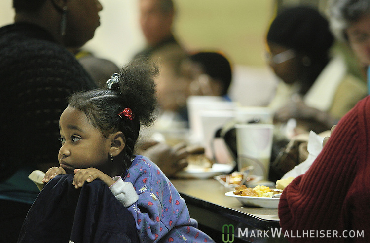 After eating, three-year-old Lakaysha Johnson's attention turns away from the Christmas dinner at the Trinity Methodist Church.  The Tallahassee Moose Lodge and the Capitol City Kiwanis Club joined together to sponsor a dinner and Christmas presents for the residents of ECHO's Bethany Family Apartments.