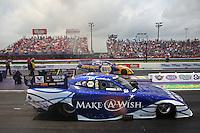 Apr 27, 2014; Baytown, TX, USA; NHRA funny car driver Tommy Johnson Jr (near lane) races alongside Ron Capps during the Spring Nationals at Royal Purple Raceway. Mandatory Credit: Mark J. Rebilas-