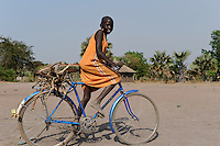 South Sudan, Rumbek, girl with bicycle transporting firewoods / SUEDSUDAN Rumbek , Maedchen transportiert Feuerholz mit dem Fahrrad