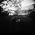 Two ladies sitting on the grass in front of the Chemical Industry pavilion at the VVC, former VDNKh. Moscow, Russia, 2009