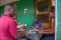 Haiti, Gros-Morne. Scholar girls through Mercy Beyond Borders doing community service at old people's home. Love-mica Dieujuste, MBB scholar, playing dominos with residents.