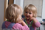 21 month old toddler girl wearing dressup necklaces looking at self in mirror recognizing self horizontal