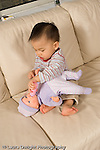 16 month old toddler boy sitting on couch pretend play feeding doll bottle vertical Asian Chinese