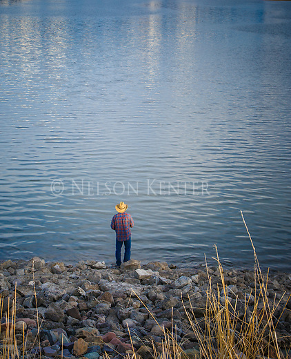 A fisherman in a straw hat and flannel shirt in western Montana on a lake shore