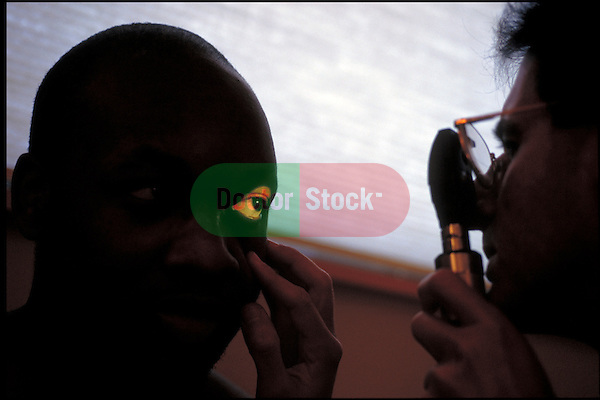 silhouette of doctor examining patient's eye