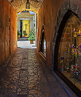 Travel Print of a narrow street with the textured walls of the buildings that lead to the main focal point of the street. Photographed in the city of Chania, Crete, in Greece.
