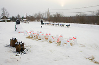 Sonny Lindner mushes down the road in Takotna just behind a dog team snow sculpture made by students of Takotna
