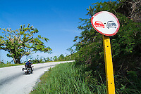 Weathered 'no overtaking' road sign and a policeman on motorbike near Trinidad, Cuba.