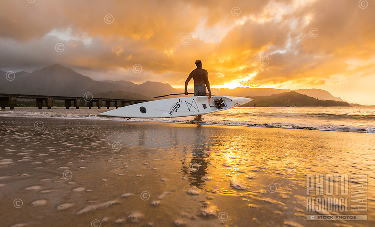 A kayaker takes his kayak out for a paddle at sunset in Hanalei Bay, Kaua'i.