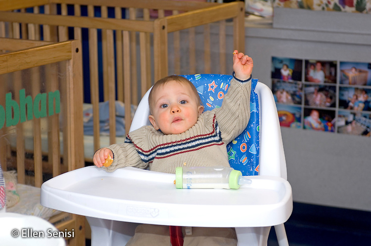 MR / Schenectady, NY.Schenectady Day Nursery / private non-profit daycare center / Infant Class.Baby boy (10 months) in high chair raises his hand..MR: Coo4.© Ellen B. Senisi