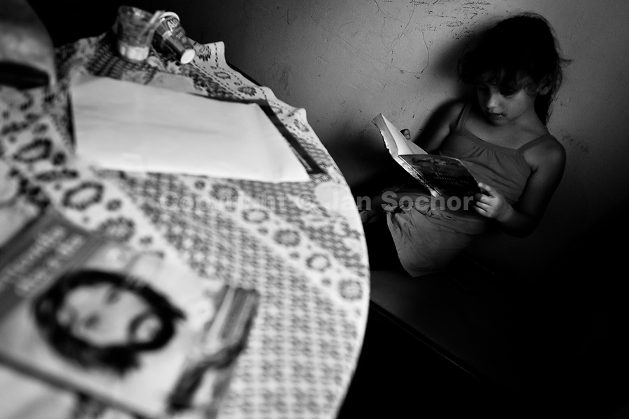 A Colombian girl reads a book in the corner during the religious ritual performed at a house church in Bogota, Colombia, 28 January 2013. Hundreds of Christian belivers, joined in nameless groups, gather every week in unmarked home churches dispersed in the city outskirts, to carry out prayers of liberation and exorcism. Community members and their religious activities are usually conducted by a charismatic pastor or preacher. Using either non-contactive methods (reading religous formulas from bible, displaying Christian symbols and icons) or rough body-pressure-points techniques and forced burping, a leading pastor commands the supposed evil spirit, which is generally believed to come from witchcraft, to depart a person's mind and body. The demon's expulsion often consists of multiple rites and may last for several months.