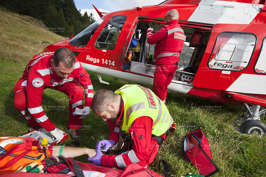 """Switzerland. Canton Ticino. Blenio valley. A Rega Agusta AW109 SP Grand """"Da Vinci"""" helicopter on pastures above Olivone. The emergency physician, Doctor Damiano Salmina, takes care of a badly injured man lying in a stretcher. The patient is a worker from the Rotex company who was injured during a logging operation. The doctor gives the prime cure for a medical treatment. He is helped by the pilot Mario Agustini (L) and the paramedic Giovanni Beldi  (standed up). Intravenous therapy. All Rega helicopters carry a crew of three: a pilot, an emergency physician, and a paramedic who is also trained to assist the pilot for radio communication, navigation, terrain/object avoidance, and winch operations. The name Rega was created by combining letters from the name """"Swiss Air Rescue Guard"""" as it was written in German (Schweizerische Rettungsflugwacht), French (Garde Aérienne Suisse de Sauvetage), and Italian (Guardia Aerea Svizzera di Soccorso). Rega is a private, non-profit air rescue service that provides emergency medical assistance in Switzerland. Rega mainly assists with mountain rescues, though it will also operate in other terrains when needed, most notably during life-threatening emergencies. As a non-profit foundation, Rega does not receive financial assistance from any government. People in distress can call for a helicopter rescue directly (phone number 1414). The AgustaWestland AW109 is a lightweight, twin-engine, helicopter built by the Italian manufacturer Leonardo S.p.A. (formerly AgustaWestland, Leonardo-Finmeccanica and Finmeccanica). Leonardo S.p.A is an Italian global high-tech company and one of the key players in aerospace. In close collaboration with the manufacturer, the Da Vinci has been specially designed to cater for Rega's particular requirements as regards carrying out operations in the mountains. It optimally fulfills the high demands made of it in terms of flying characteristics, emergency medical equipment and maintenance. Safety, performance a"""