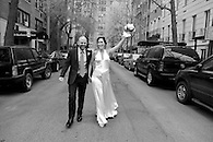 Exuberant shot of bride and groom walking down the street with bride holding up her bouquet.