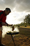 A man grills a steak on an outdoor barbeque in Northern Arizona, United States of America. (backlit)