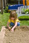 MR / Schenectady, NY. Girl (4) plants seedling in family garden in raised bed in back yard. MR: Jan3. ID: SPR. © Ellen B. Senisi
