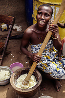 Cote d'Ivoire, Ivory Coast, West Africa.  Young Woman Pounding Yams for next Meal.  Lolobo Village near Bouake.