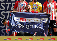 29th May 2021; Wembley Stadium, London, England; English Football League Championship Football, Playoff Final, Brentford FC versus Swansea City; Emiliano Marcondes of Brentford celebrates with a We're Going Up banner after they won 2-0 and promoted to the premier league