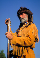 Western scene. A man clad in a leather fringed jacket and raccoon fur hat costume portrays a western mountain man demonstrating the procedure of loading an old-fashioned rifle. Register Rock Idaho, Register Rock State Park.
