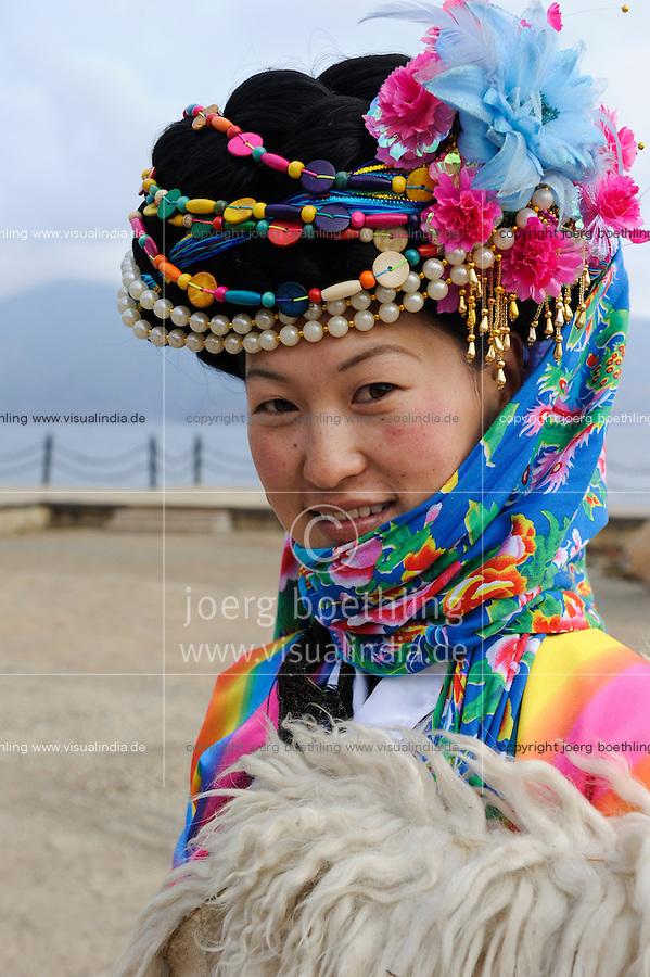 CHINA Yunnan Lugu Lake , ethnic minority Mosuo who are buddhist and women have a matriarch, Mosuo woman in traditional clothes / CHINA Provinz Yunnan , ethnische Minderheit Mosuo am Lugu See , die Mosuo sind Buddhisten und Mosuo Frauen ueben ein Matriarchat aus