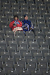 Hertha Berlin 1 Sporting Lisbon 0, 16/12/2010. Olympic Stadium, Europa League. Two home fans attempt to keep warm inside the stadium before Hertha Berlin's match against  Sporting Lisbon at the Olympic Stadium in Berlin in the group stages of the UEFA Europa League. Hertha won the match by 1 goal to nil to press to the knock-out round of the cup. 2009/10 was the the first year in which the Europa League replaced the UEFA Cup in European football competition. Photo by Colin McPherson.