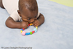5 month old baby boy African American  closeup on stomach grasping and mouthing biting toy horizontal