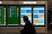 A man passes a flight board and a healthcare information sign at the international terminal at Dulles International Airport in Dulles, Va., Monday, March16, 2020. Some people are taking the precaution of wearing face masks as they arrive to be greeted by family and or friends. Credit: Rod Lamkey / CNP