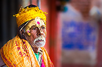 Portrait of a Hindu Sadhu holy man with painted face and colorful clothing, during Holi celebrations in Mathura Uttar Pradesh India