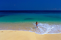 A small boy runs into the beautiful, calm blue ocean at a white sand beach on the windward side of Oahu.