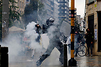 BOGOTA, COLOMBIA - MAY 05: A police officer throw a  gas canisters during national strike on May 5, 2021 in Bogota, Colombia. Despite that the ruling party announced withdrawal of the unpopular bill for a tax reform and the resignation of the Minister of Finances, social unrest continues after a week. The United Nations human rights office (OHCHR) showed its concern and condemned the riot police repression. Ongoing protests take place in major cities since April 28. (Photo by Leonardo Munoz/VIEW press/Corbis via Getty Images)