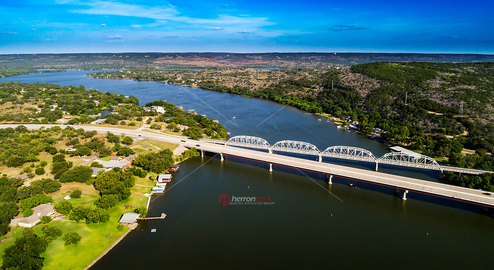 In this image you can see the old Inks Lake SH 29, Bridge next to the new bridge overlooking the pristine Inks Lake. is the next lake down the Colorado River from Lake Buchanan.  It starts just a short distance from the base of Buchanan Dam.  With a length of 4.2 miles and a width of 3,000 feet, Inks Lake is the shortest of the first four lakes but is also one of the most beautiful lakes in Texas.<br /> <br /> State Highway 29 Bridge at the Colorado River is located in both Burnet and Llano counties in the U.S. state of Texas, between Buchanan Dam and Inks Lake . It is also known as Inks Lake Bridge, and was added to the National Register of Historic Places listings in both counties on October 10, 1996. The 1,379 ft truss bridge was planned by the Texas Highway Department in 1929. Construction was completed by the Austin Bridge Company in 1937 at a cost of $188,000. A new four-lane vehicular bridge was built in 2005, and the old SH 29 Bridge is currently open only to pedestrians.