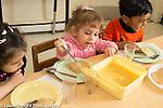 Preschool 2-3 year olds breakfast time girl serving self applesauce