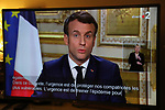 March 12, 2020, shows a TV screen broadcasting the declaration of France's President Emmanuel Macron, made from The Elysee Palace in Paris, about the situation of the COVID-19 outbreak in France, caused by the novel coronavirus. Emmanuel Macron announced schools in France would close from next Monday and urged people over 70 to stay at home, to curb the spread of the coronavirus. French president also announced that local elections to be held on March 15, will not be postponed.