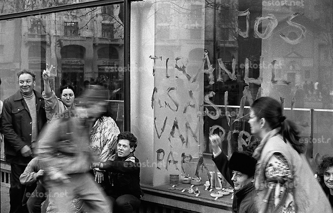"""ROMANIA, Magheru Bd., Bucharest, 22.12.1989, 4 pm..Magheru boulevard in the centre: More than one million people are celebrating Ceausescu's running away. On the window it is written """"Down with the tyran, killer, vampire, paranoid"""".© Andrei Pandele / EST&OST"""