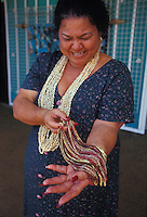 Rare and valuable Niihau Shell Necklace of Kahelelani shells held by Hawaiian woman
