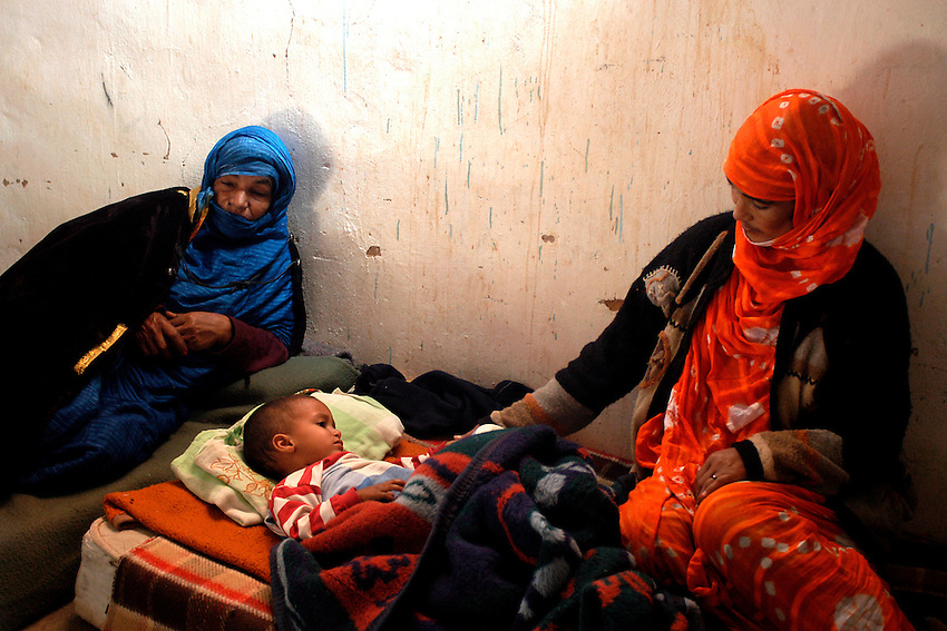 Two women take care for a child in a hospital on December 13, 2003. Saharawi people have been living at the refugee camps of the Algerian desert named Hamada, or desert of the deserts, for more than 30 years now. Saharawi people have suffered the consecuences of European colonialism and the war against occupation by Moroccan forces. Polisario and Moroccan Army are in conflict since 1975 when Hassan II, Moroccan King in 1975, sent more than 250.000 civilians and soldiers to colonize the Western Sahara when Spain left the country. Since 1991 they are in a peace process without any outcome so far. (Ander Gillenea / Bostok Photo)