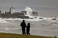 Pictured: Two people walk their dog as waves crash against the promenade wall and lighthouse in Porthcawl, south Wales, UK. Saturday 15 February 2020<br /> Re: Strong winds and heavy rain caused by storm Dennis has been affecting parts of the UK.