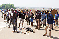 Isaac Mofali lies dying after being mortally wounded in close quarters fighting between the Red Ants and a community of people defending their homes built on squatted land in Vlakfontein. The Red Ants were carrying out a so-called 'demolition' operation to clear the dwellings and evict the squatters but the violent action resulted in the deaths of two people from among the community of squatters. The Red Ants are a controversial private security company often hired to clear squatters from land and so-called 'hijacked' properties.
