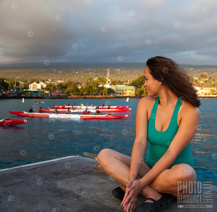 A woman on the Kailua Kona pier watches outrigger canoe paddlers practice in Kailua Bay, Big Island. (Note: She is model released, but the others are not.)