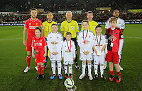 SWANSEA, WALES - MARCH 16: Children mascots with team captains Jordan Henderson of Liverpool (L) and Ashley Williams (R) of Swansea and match officials Roger East referee (C)<br /> Re: Premier League match between Swansea City and Liverpool at the Liberty Stadium on March 16, 2015 in Swansea, Wales