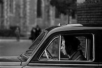 """Tournage du film """"La Bourse ou la Vie"""" de Jean Pierre Mocky, dans le quartier de St Sernin, Tououse, France, novembre 1965<br /> <br /> 2 novembre 1965. Plan rapproché de l'acteur Jean Poiret dans une voiture fermant les yeux. Par la fenètre entrouverte de la voiture, le réalisateur jean-Pierre Mocky de profil, lors d'une scène de tournage.<br /> <br /> PHOTO:  Fonds André Cros,"""