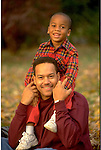 portrait of father with young son sitting on his shoulders