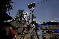 Elie Paul Dieme repairs a solar powered street lamp.