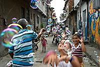 Seu João Bolinha ( Mr. John Soapbubble ), as he is known in the streets of Favela da Maré in Rio de Janeiro, street vendor of soapbubbles, makes children happy when he passes. Brazil. Children interacting with neighbors and community.