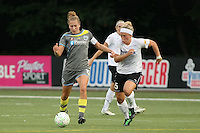 Philadelphia captain, defender Nikki Krzysik(15), passes the ball as magicjack forward, Ella Masar (55) gives chase.  With five different players scoring, the Philadephia Independence overpowered magicjack, 6-0 on June 18th at Widener University in Chester, PA.